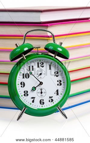 Big green alarm clock with pile of books, isolated on white background
