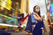 stock photo of going out business sale  - beautiful woman goes shopping in the city - JPG