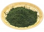 small bowl of Hawaiian spirulina powder against a rough white painted barn wood background