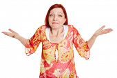Clueless elderly woman shrugging with her shoulders