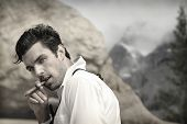 stock photo of cigar  - Sexy hunky male model outdoors smoking cigar with seductive look and vintage feel - JPG
