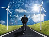 Businessman standing in middle of road with wind turbines either side looking at graphs on the horiz