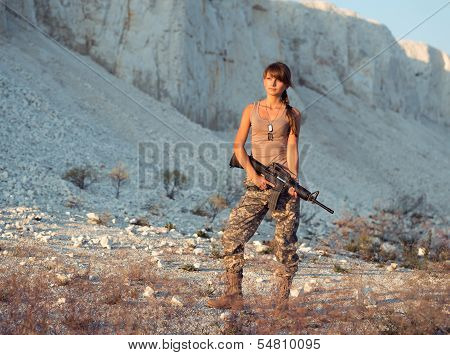 Young Female Soldier Dressed In A Camouflage With A Gun In The Location