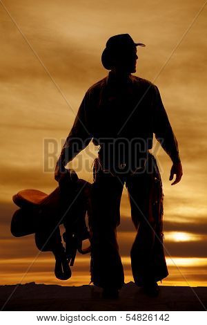 Silhouette Man Holding A Saddle By Side