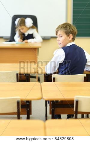 Girl sits at teacher table and writes and boy sits at desk and looks away in classroom at school. Focus on boy.