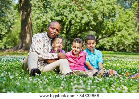 Father and three sons sit on ground in summer park