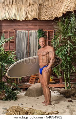 Muscular man in trunks on a sandy beach with a surfboard in hand