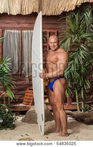 Muscular man in trunks on a sandy beach with a surfboard