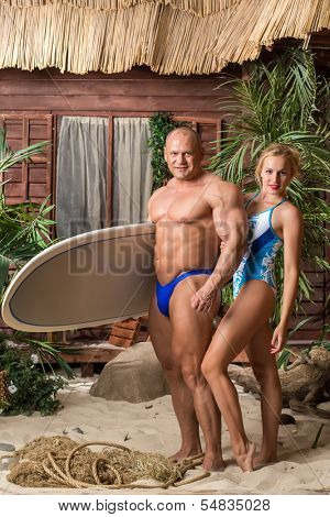 Muscular man in trunks and beautiful girl in swimsuit with a surfboard on a sandy beach