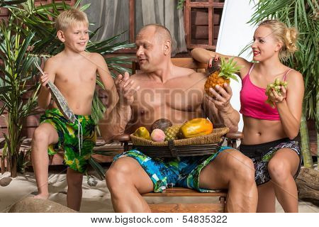 A family of three on a beach with a basket of fruit and fish