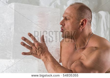 A strong man with big muscles blowing on ice cube