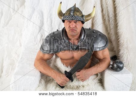A menacing muscular man in costume viking with a sword and fur