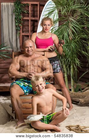 A family of three on a sandy beach, focus on a boy with fish.