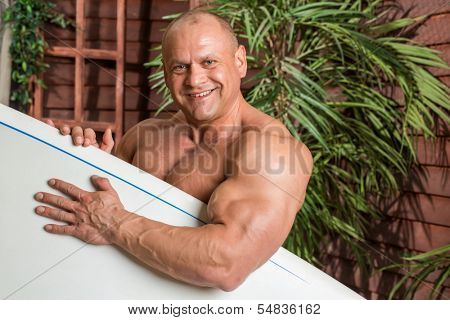 Smiling muscular man on a beach with a surfboard near the wooden house