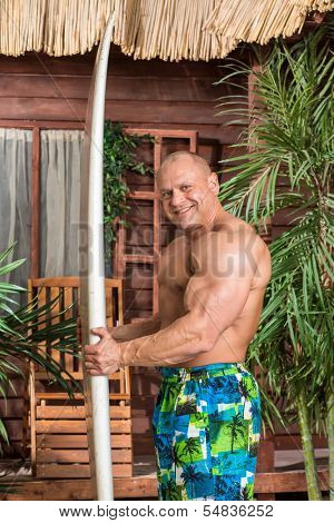 Smiling muscular man in short on a beach with a surfboard