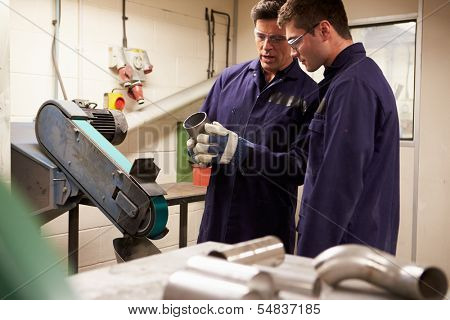 Engineer Teaching Apprentice To Use Grinding Machine
