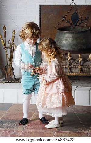 Little boy and girl in medieval costumes look at small casket near fireplace with boiler.