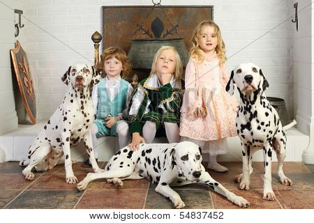 Two boys and girl in medieval costumes rest near fireplace with hanging pot with dalmatians.