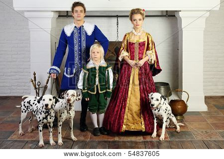 Father, mother and son in medieval costumes stand near fireplace with three dalmatians.