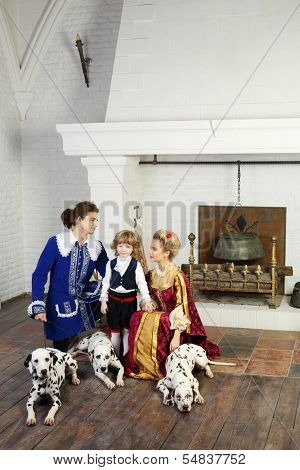 Young father, mother in medieval costumes look at little son near fireplace with three dalmatians on leashes.