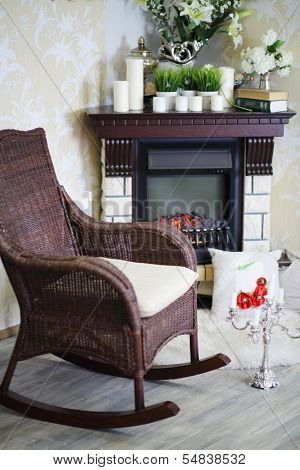 Wicker rocking chair, candlestick and fireplace with candles and flowers in cosy room.