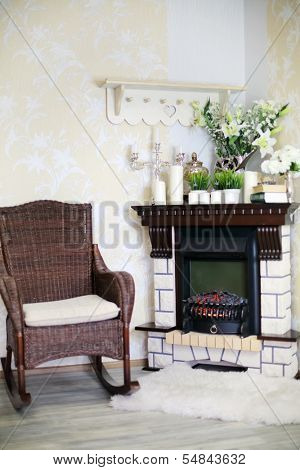 Wicker rocking chair and fireplace with candles and flowers in cosy room.