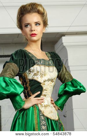 Beautiful young woman in luxury green medieval costume looks away.