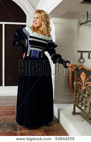 Beautiful woman in medieval costume stands near fireplace and looks away.