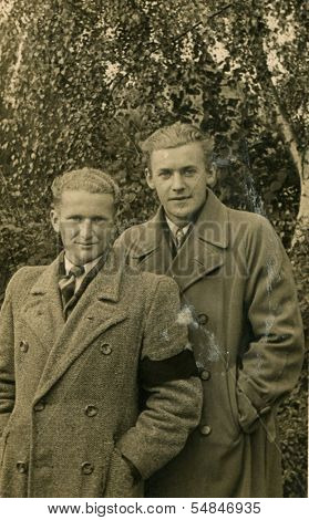 WESTPHALIA, GERMANY, SEPTEMBER 20: Vintage photo of two men in coats, one of them with armband for mourner, Westphalia, Germany, on September 20, 1940
