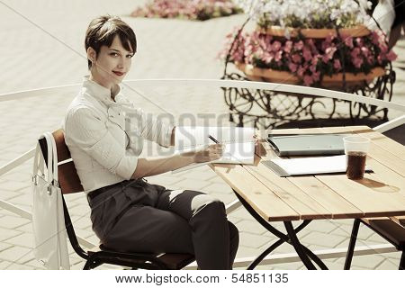 Young business woman working at a sidewalk cafe