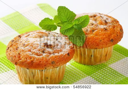 detail of two muffins with chocolate chips on a green square linen