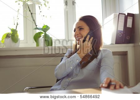 Pretty Woman Talking On Mobile Phone In Home Office