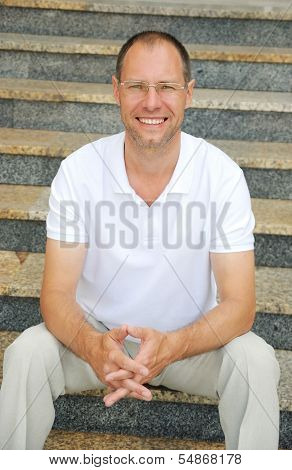 Middle Age Man Sitting On The Steps