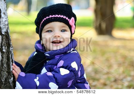 Cute little girl playing in autumn park near tree, nature outdoor