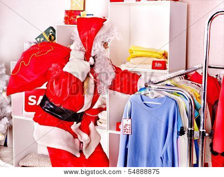 Santa Claus in clothing store. Christmas sale.