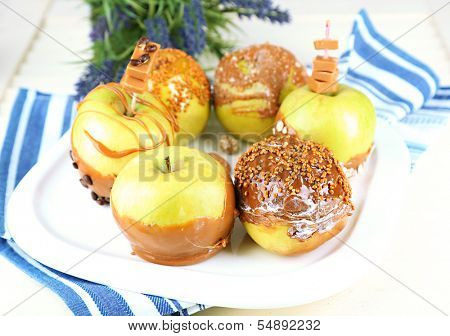 Homemade taffy apples, on napkin, on wooden background
