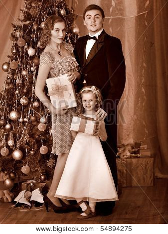 Family with children  dressing Christmas tree. Black and white retro.