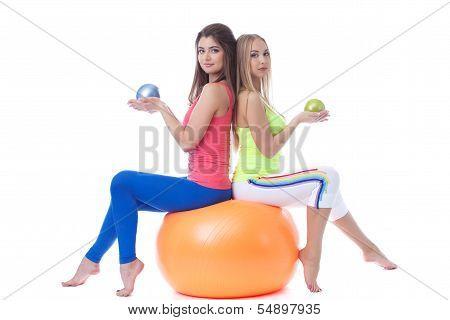 Attractive sportswomen sitting on gymnastic ball