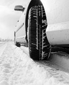 stock photo of slippery-roads  - Close up of a car tires on a snowy road - JPG