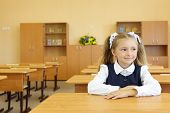 Little girl in school uniform sits at school desk and looks away in classroom in first grade for her