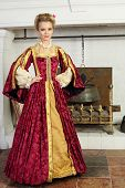 Beautiful woman in red medieval costume stands near fireplace with logs and boiler.