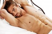 stock photo of undressing  - Handsome nude man lying in a bed - JPG