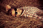 picture of haystacks  - Handsome young man lying in haystack - JPG