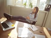 stock photo of thoughtfulness  - Young beautiful businesswoman at table resting with her legs on desk - JPG