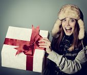 stock photo of rapture  - Cute excited christmas girl in winter hat opening gift box - JPG