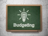 Business concept: Light Bulb and Budgeting on chalkboard