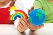 Environmental awareness and education concept - child hands holding earth globe and rainbow made of