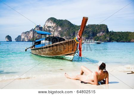 Exotic beach holiday - woman sunbathing and longtail boat in the background