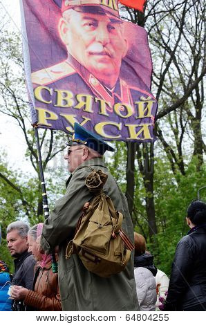 Man hold flag with portrait of Joseph Stalin Soviet Union leader during Victory Day holiday