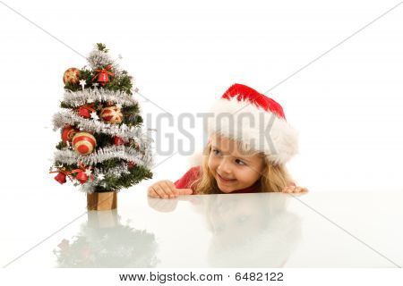 Happy Kid Lurking Around A Small Christmas Tree